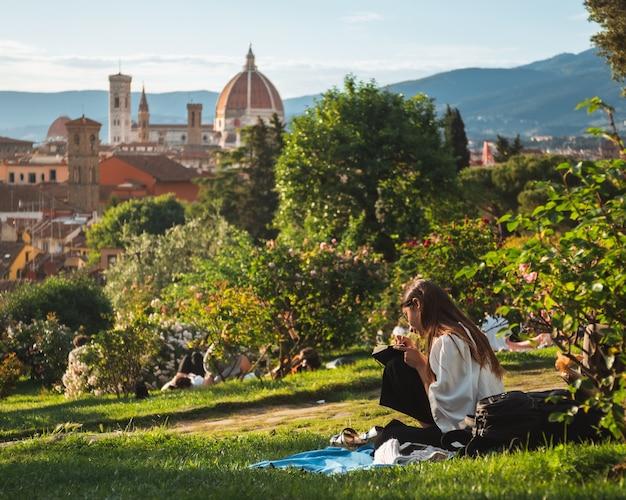 Meisje zittend op het gras met een prachtig uitzicht over florence Gratis Foto