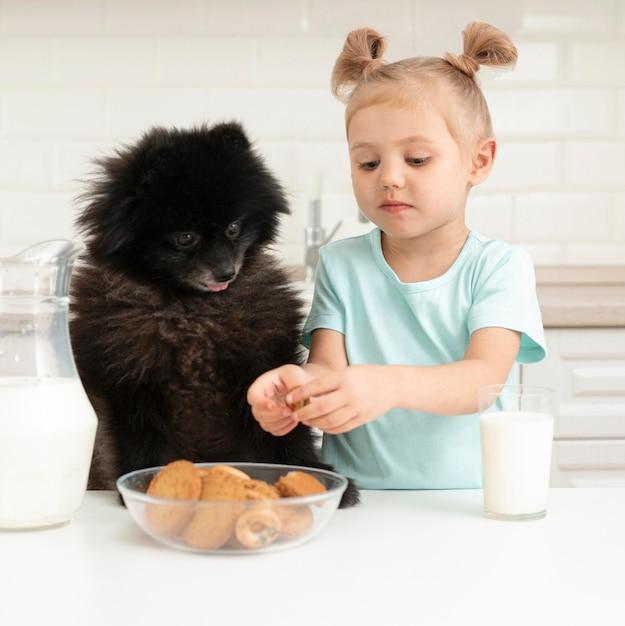 Meisjeconsumptiemelk en het spelen met hond Gratis Foto