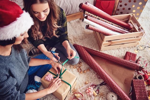 Meisjes die een cadeau voorbereiden voor kerstmis Gratis Foto