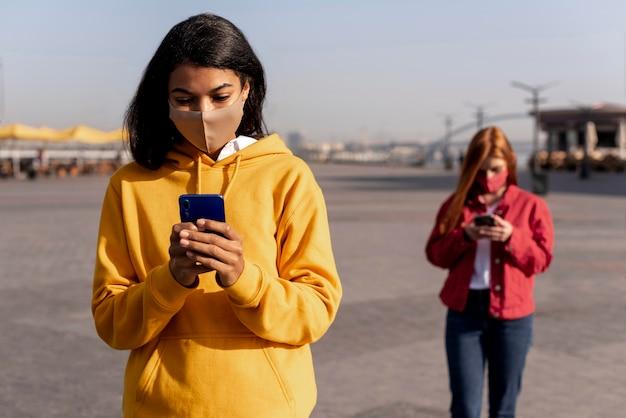 Meisjes die medische maskers dragen terwijl ze sociale afstand nemen Gratis Foto