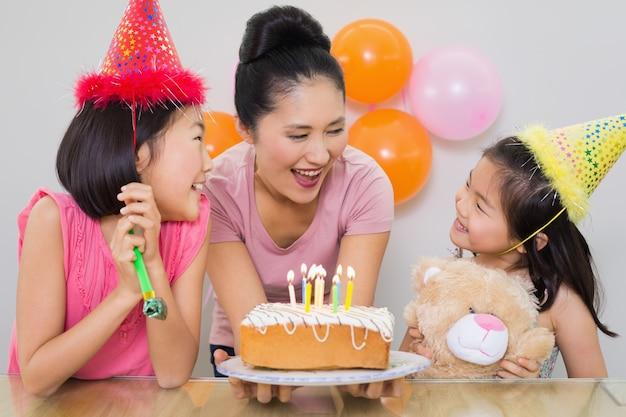 Meisjes die moeder met cake bekijken bij een verjaardagspartij Premium Foto