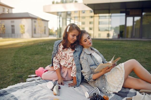 Meisjes die op een deken in een de zomerpark zitten Gratis Foto