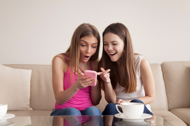 Meisjes die op grappige foto's op cellphone kijken Gratis Foto