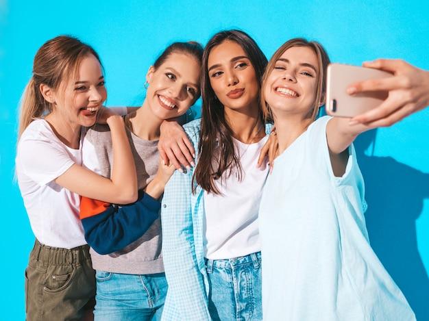 Meisjes die selfie zelfportretfoto's op smartphone nemen modellen die dichtbij blauwe muur in studio, wijfje stellen die positieve gezichtsemoties tonen Gratis Foto