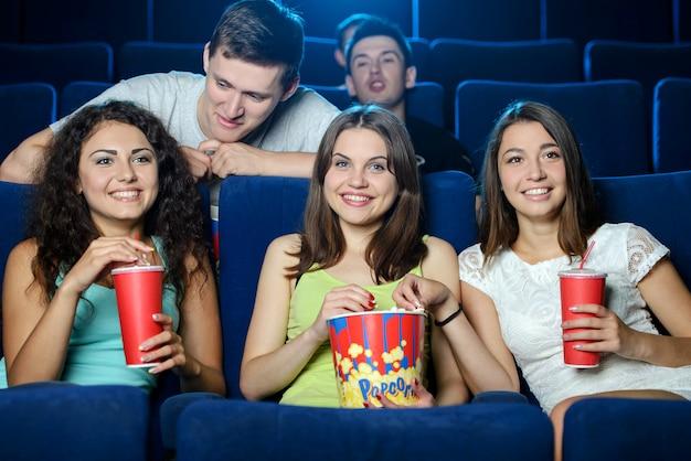 Meisjes en jongens zitten op stoelen en kijken films. Premium Foto