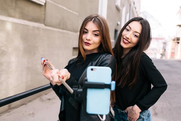 Meisjes glimlachen terwijl het nemen van een foto Gratis Foto