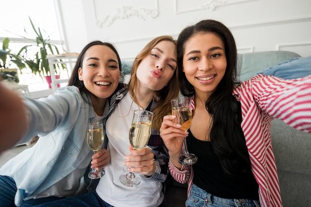 Meisjes houden van een bril met een drankje en nemen selfies Gratis Foto