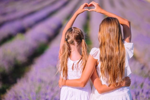 Meisjes in lavendelbloemen veld bij zonsondergang in witte jurken Premium Foto
