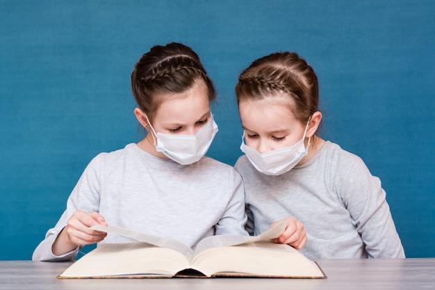 Meisjes in medische maskers in quarantaine lezen zorgvuldig een boek aan tafel. kinderen opvoeden in een epidemie Premium Foto