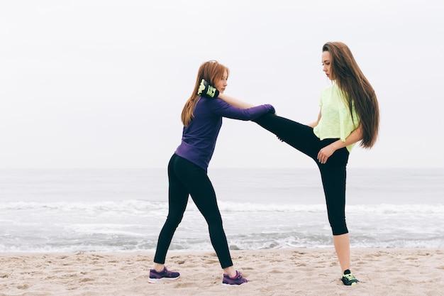Meisjes in sportkleding worden uitgerekt op het strand Premium Foto