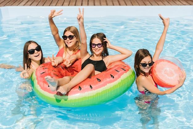 Meisjes in zwembad dat vredesteken toont Gratis Foto