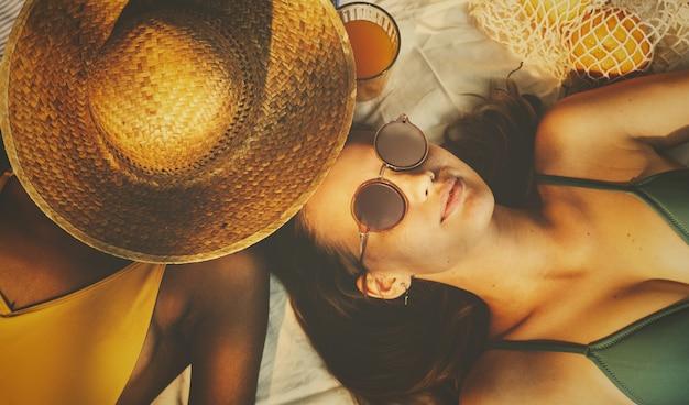 Meisjes in zwemkleding die in de zon ontspannen Premium Foto