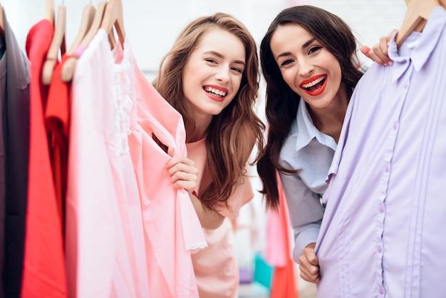 Meisjes kiezen kleding in de modewinkel. Premium Foto