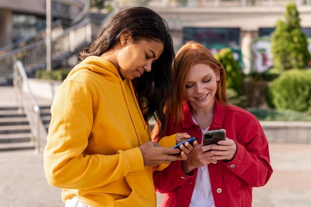 Meisjes kijken op hun telefoons Gratis Foto