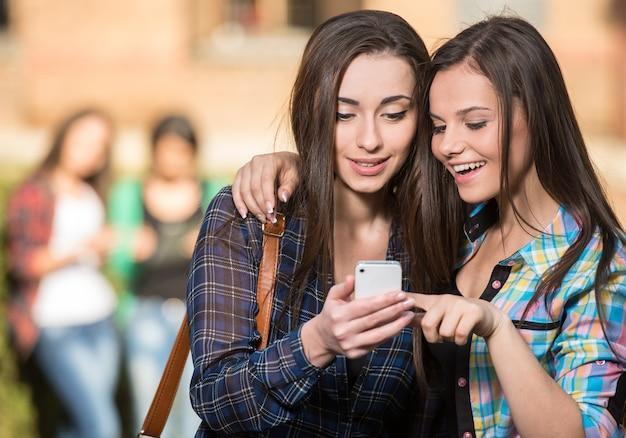 Meisjes knuffel en iets kijkt naar de telefoon. Premium Foto