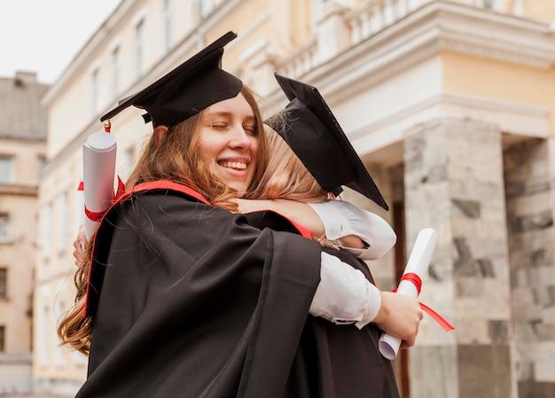 Meisjes knuffelen bij afstuderen Gratis Foto
