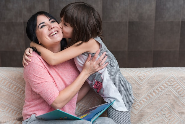 Meisjes kussende moeder met boek op wang Gratis Foto