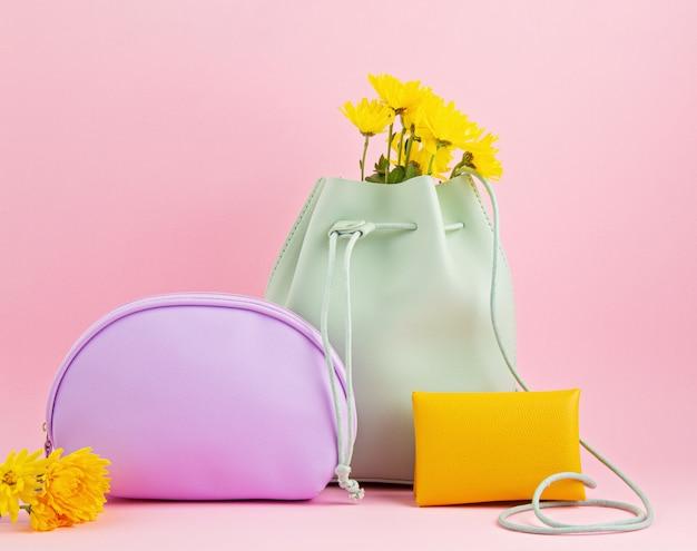 Meisjes leren accessoires in felle pastelkleuren: handtas, handtas, make-uptasje en bloemen over roze achtergrondkleur Premium Foto