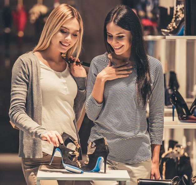 Meisjes met boodschappentassen kiezen schoenen en glimlachen Premium Foto