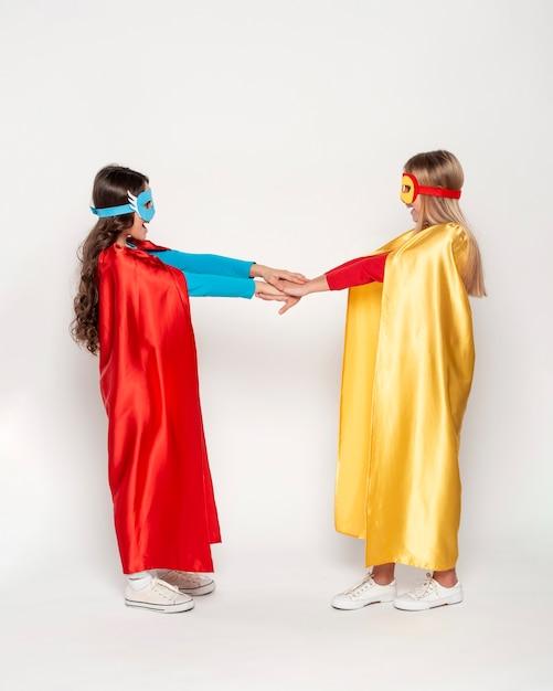 Meisjes met helden kostuum hand in hand Gratis Foto