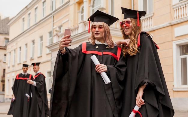 Meisjes nemen selfie bij afstuderen Gratis Foto