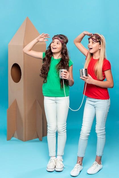 Meisjes spelen vlieger met cartoon vliegend schip Gratis Foto