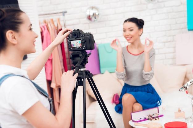 Meisjes steken oorbellen op met een meisje achter de camera Premium Foto