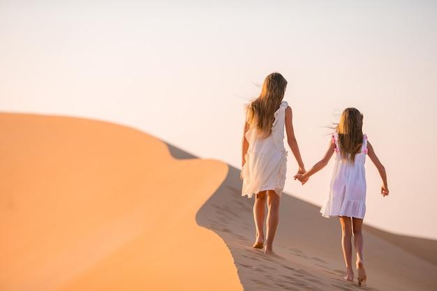 Meisjes tussen de duinen in de rub al-khali-woestijn in de verenigde arabische emiraten Premium Foto