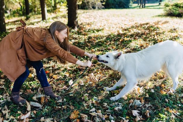 Meisjesgangen bij de herfstpark met jonge witte zwitserse herdershond Premium Foto