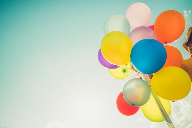 Meisjeshand die veelkleurige ballons houden Premium Foto