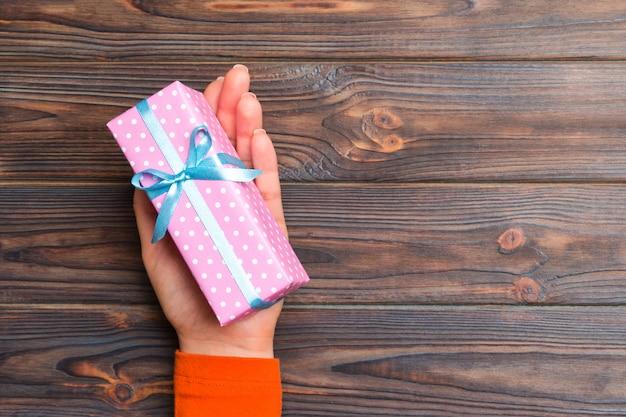 Meisjeshanden die ambachtdocument giftvakje houden voor kerstmis op donkere houten achtergrond Premium Foto