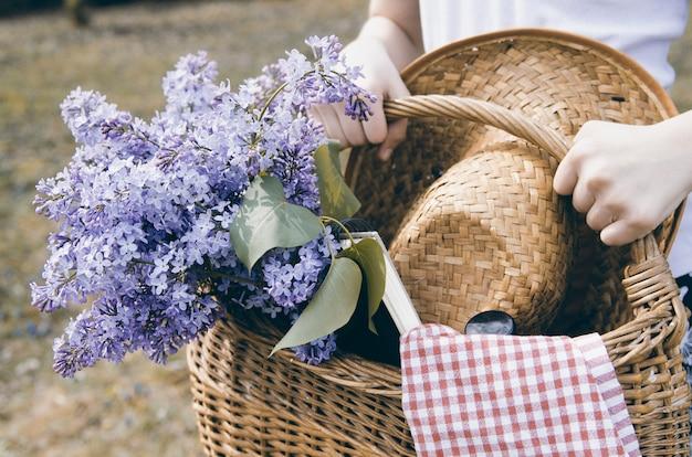 Meisjeshanden die rieten mand met lilac bloemboeket dragen Premium Foto