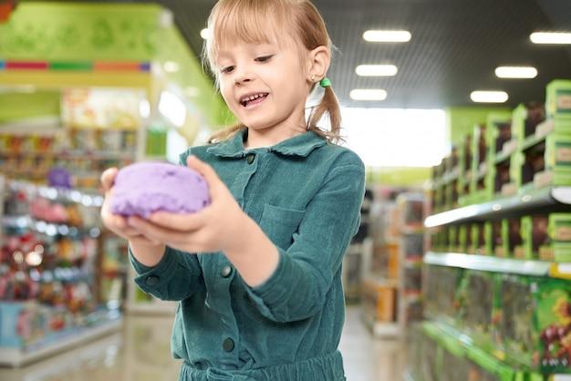 Meisjesholding in handen violet kinetisch zand, die bij camera stellen. Gratis Foto