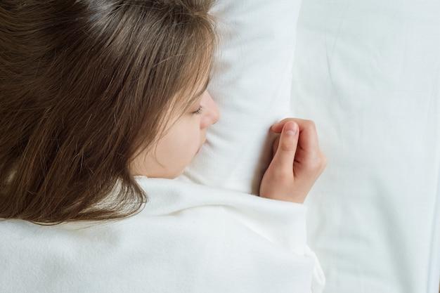 Meisjeskind met lang bruin haar slapen op een kussen in bed Premium Foto