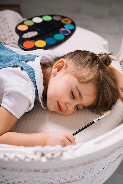 Meisjeslaap op bank met helder aquarelpalet Gratis Foto