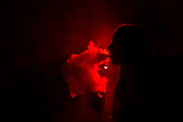 Meisjesmodel rookt vape in rood licht. detailopname. Premium Foto