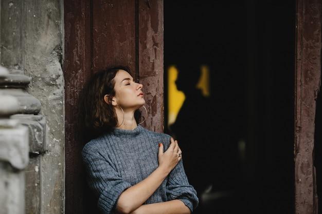 Meisjesportret dichtbij een oude de bouwdeur en op ger achtergrond is er een yong mensensilhouet Gratis Foto