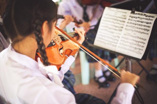 Meisjesstudenten die viool in de groep spelen. Premium Foto