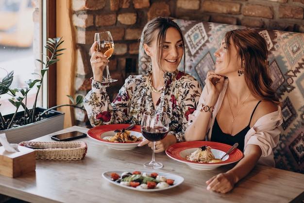 Meisjesvrienden die deegwaren in een italiaans restaurant eten Gratis Foto