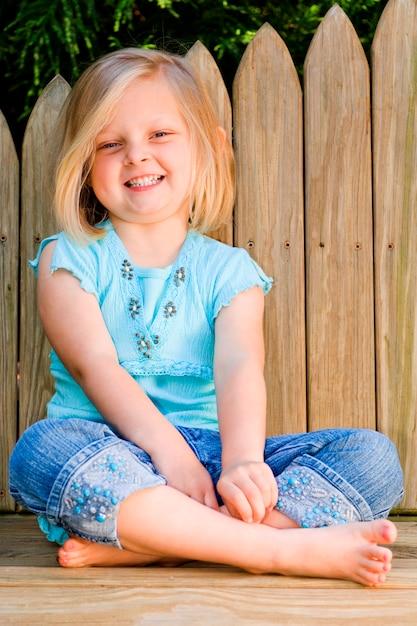 Meisjeszitting door houten omheining, het glimlachen, portret Premium Foto