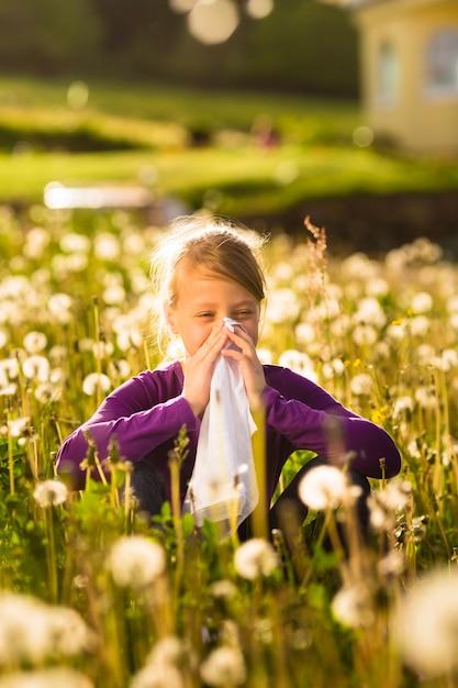Meisjeszitting in weide met paardebloemen en heeft hooikoorts of allergie Premium Foto