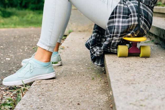 Meisjeszitting op een skateboard in het park Premium Foto