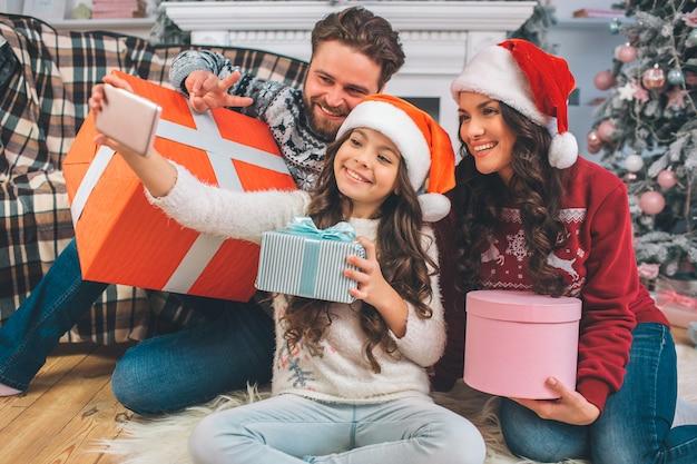 Meisjeszitting op vloer ith haar ouders en telefoon in handen houden. ze neemt een foto van hen. en mensen die stellen glimlachen. elk van hen heeft doos aanwezig in handen. Premium Foto