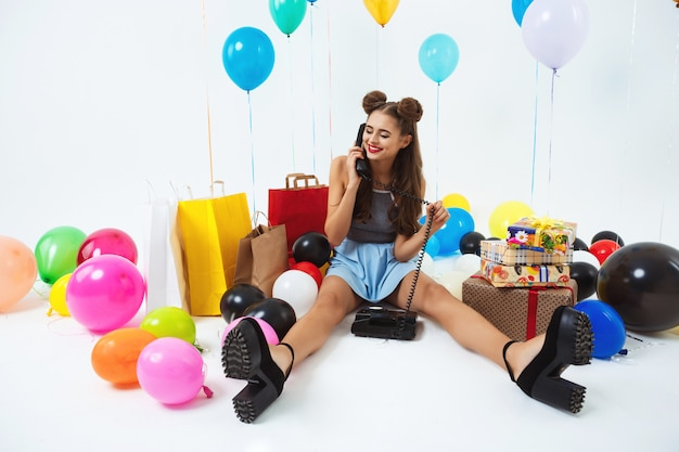 Meisjeszitting op vloer met huistelefoon, die verjaardagswensen ontvangen Gratis Foto