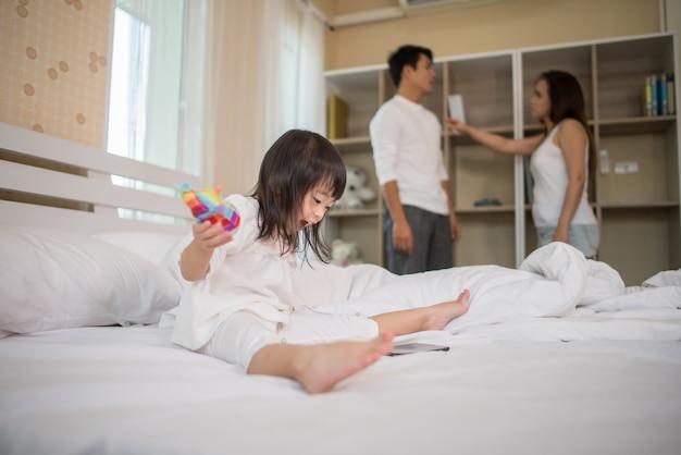 Meisjezitting met haar ouders op het bed dat ernstig kijkt Gratis Foto