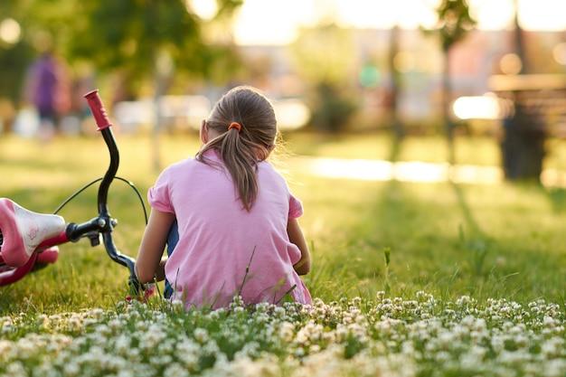 Meisjezitting op het gras dichtbij haar fiets bij zonsondergang Premium Foto