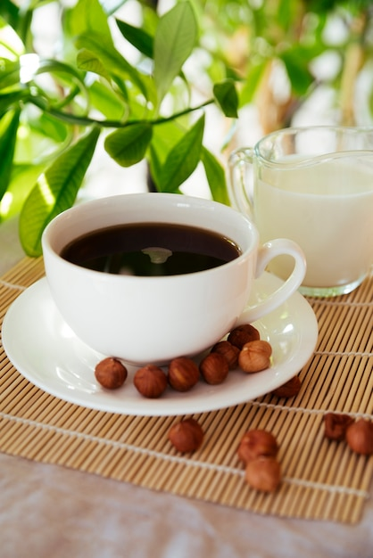 Melk en koffiekop op bamboemat Gratis Foto