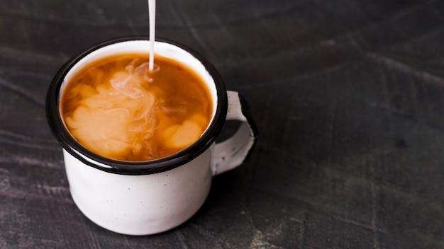 Melk gegoten in zwarte koffie Gratis Foto