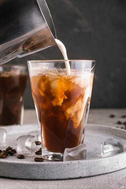 Melk gieten in glas met koffie Gratis Foto