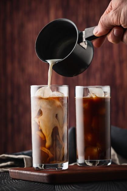 Melk gieten in ijskoffie Premium Foto